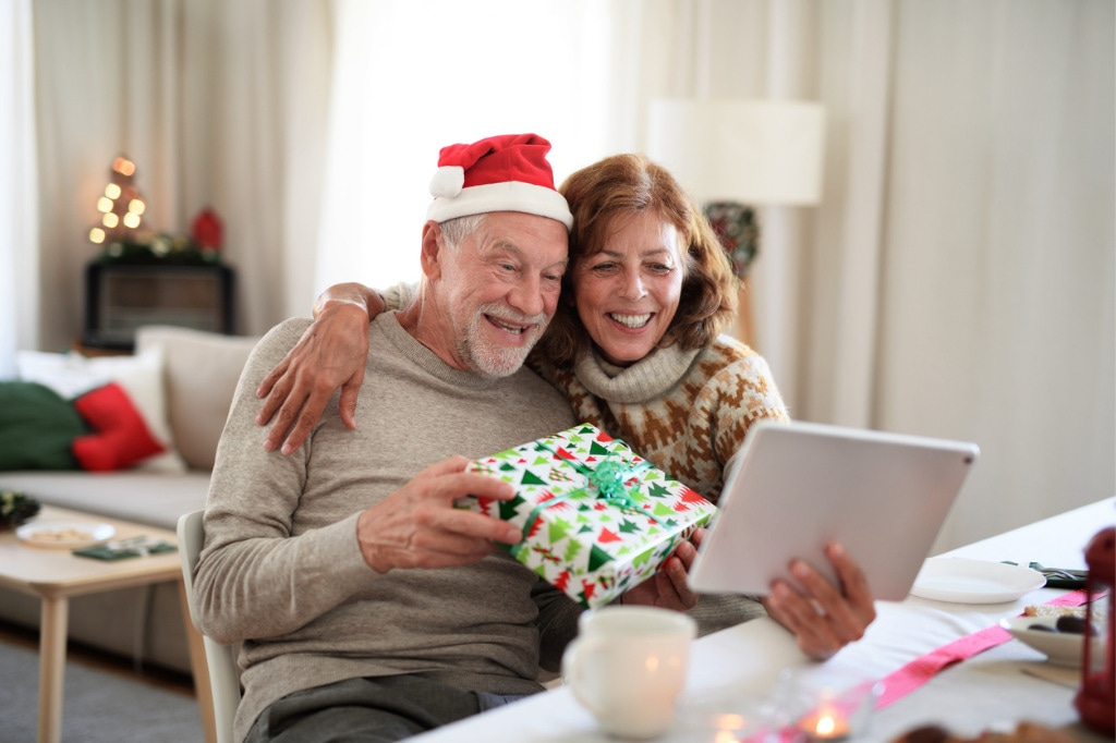 front-view-of-senior-couple-indoors-at-home-at-christmas-having-video-picture-id1279002577.jpg
